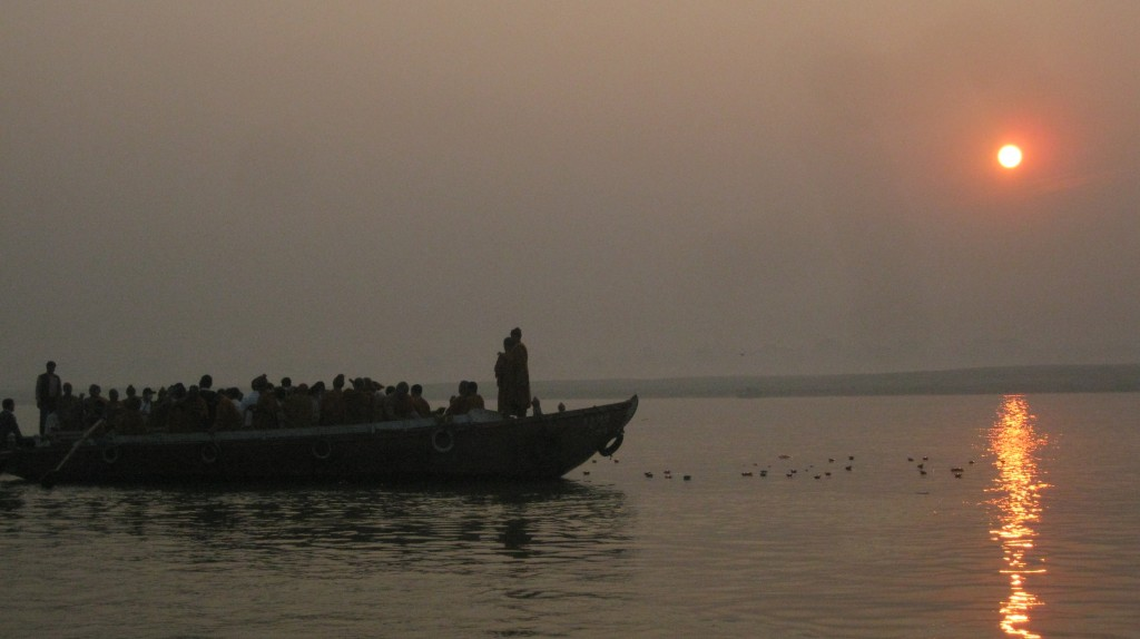 Buddhist monks against a Ganges sunrise.