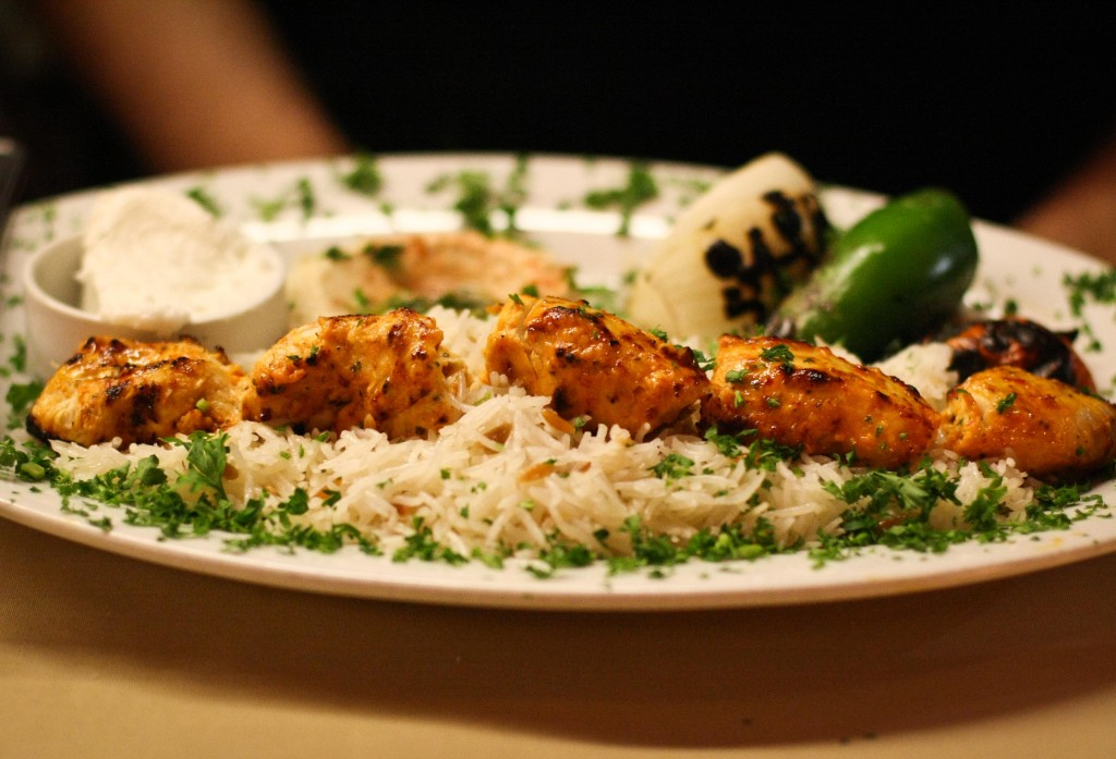 Chicken Kebab Plate - Skewered cubes of marinated, charbroiled chicken tenders, served with hummus, rice pilaf, garlic sauce, grilled veggies and pita bread.