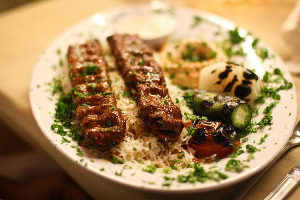 Adana Kabab Plate - Skewers of extra lean ground beef mixed with parsley, onion, spices, charbroiled and served with hummus, rice pilaf, tahini sauce, grilled veggies and pita bread.