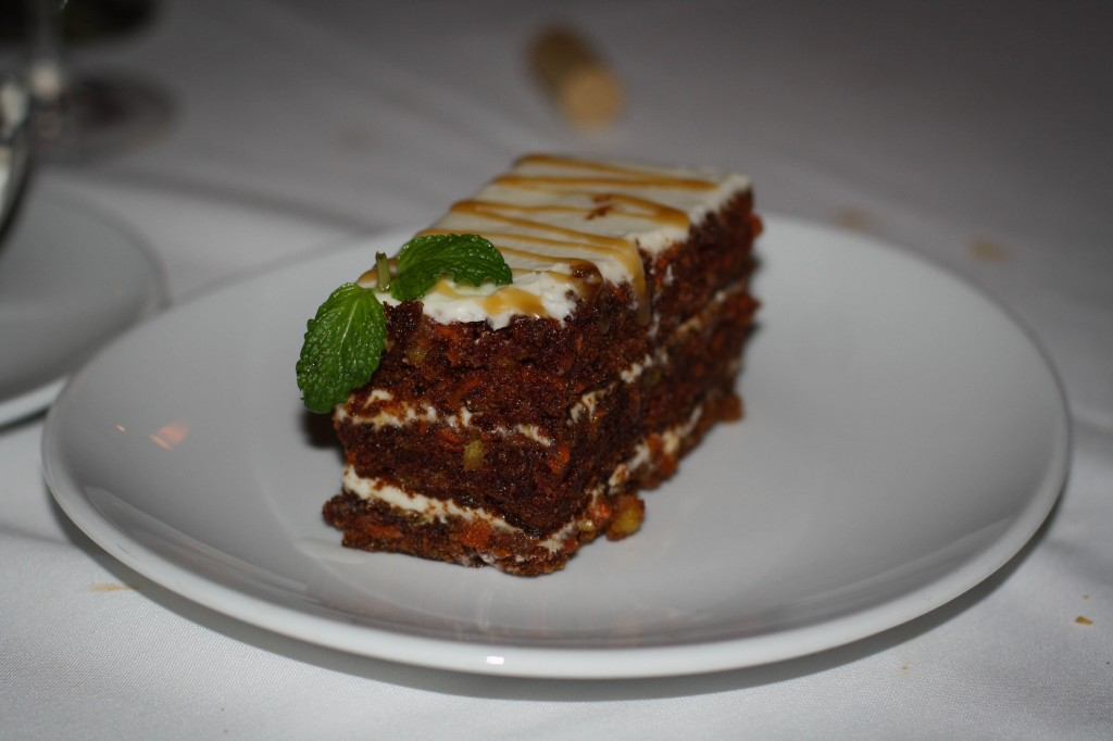 CARROT CAKE  three layer cake with cream cheese frosting topped with a drizzle of dark rum caramel