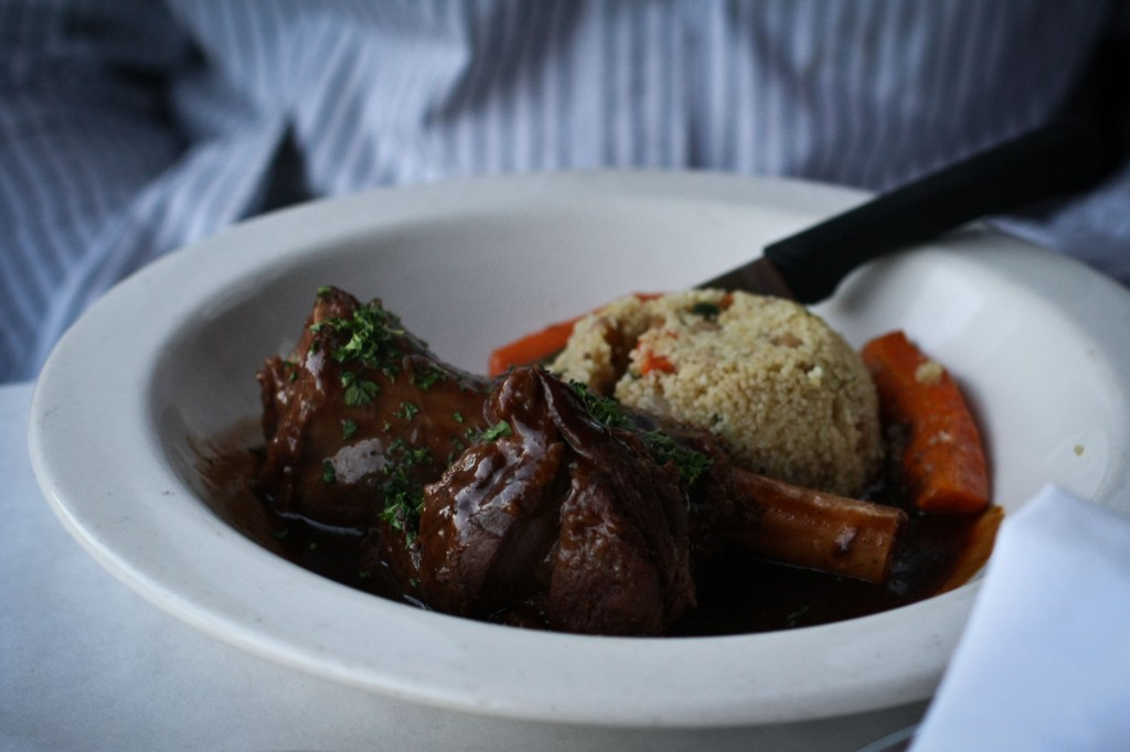 BAKED LAMB SHANK in a red wine vegetable sauce served with couscous & carrots
