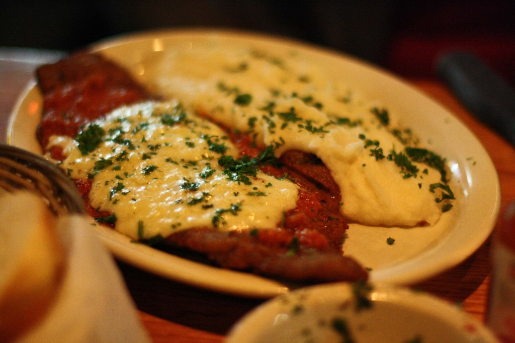 Milanesa Napolitana -   thinly cut steak, breaded & lightly fried, topped with basil tomato sauce & melted cheese, served with mashed potatoes