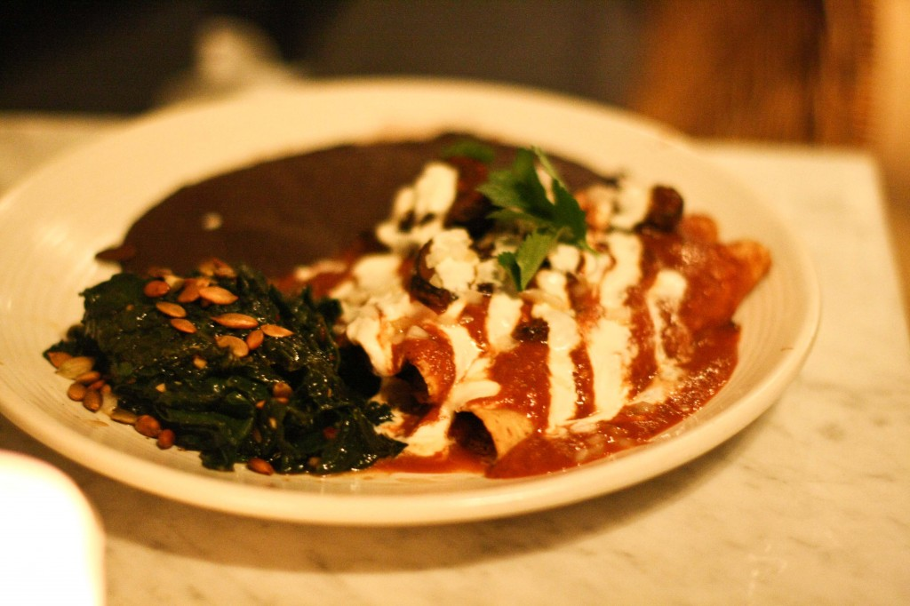 ENCHILADAS CON MOLE Spicy mole enchiladas topped with mushrooms and cashew cheese, served with sautéed greens and beans