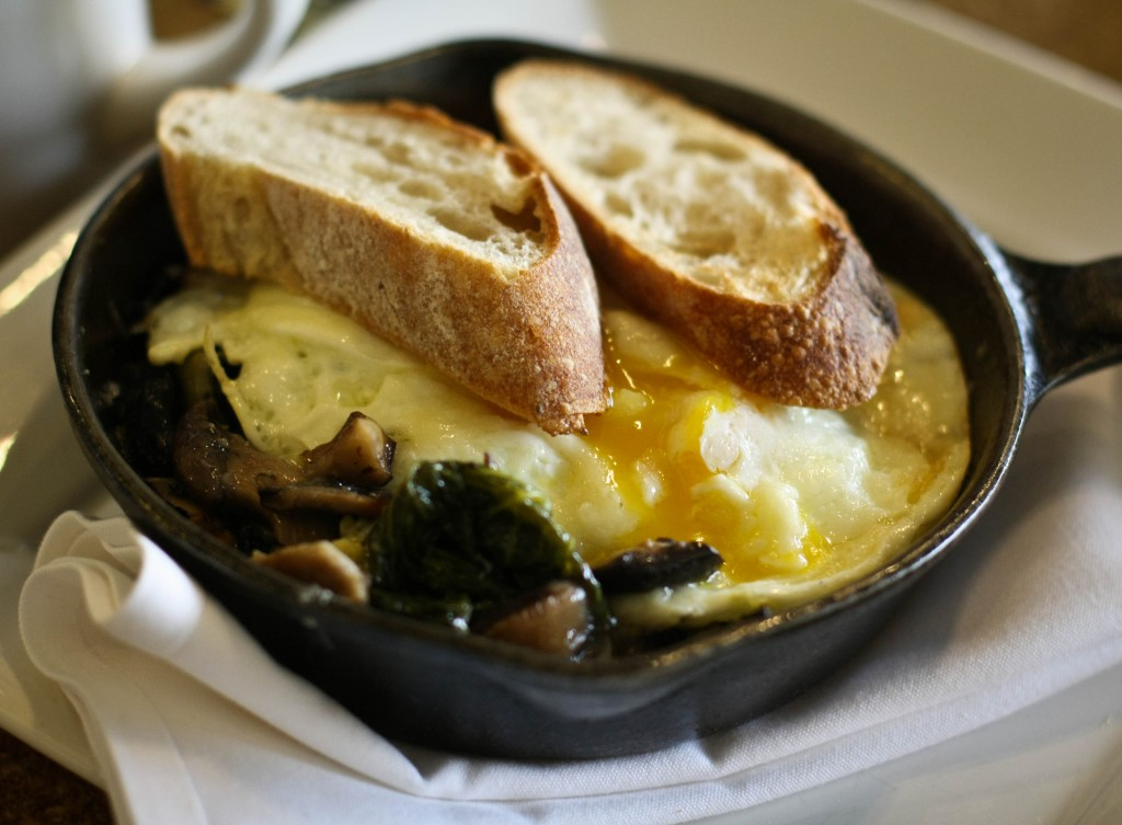 Baked Eggs - braised mustard and collard greens with mushrooms and gruyere on grits